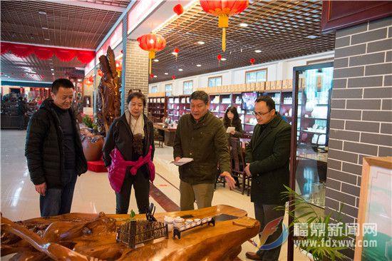 导演林小龙(右二)对根雕茶座十分感兴趣.jpg