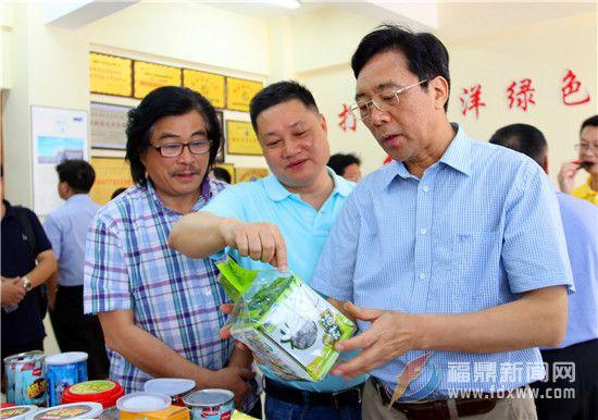 陈荣凯向企业详细了解产品外包装的相关工序。.jpg